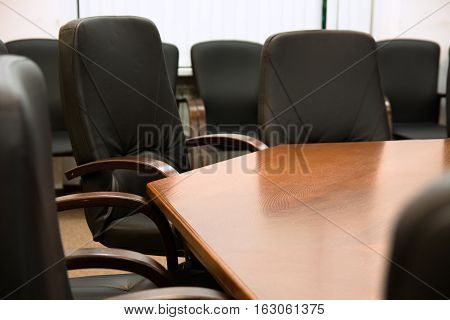 Black Leather Chairs Around A Wooden Table
