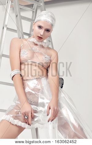 Girl Shows Clothing Made Of Cellophane And Foil