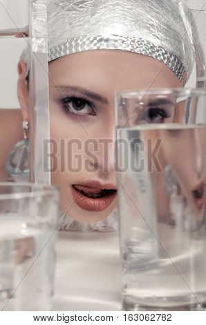 Girl Looks Through Glasses Filled With Water