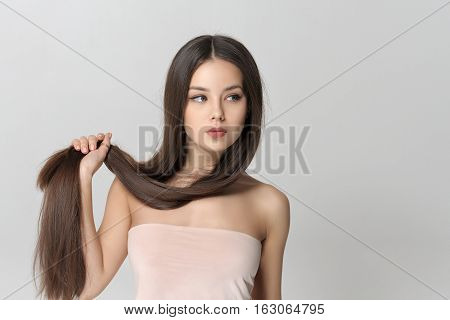 Girl Holds Her Long Hair On Her Arm