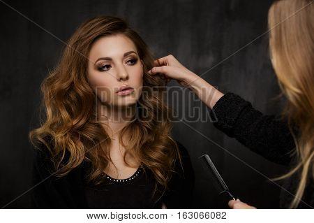 Stylist corrects hair of beautiful girl in studio