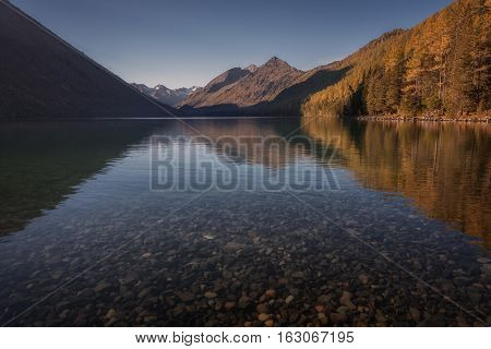 Shallow Mountain Lake With Mirror Like Surface , Altai Mountains Highland Nature Autumn Landscape Photo. Beautiful Russian Wilderness Scenery Image.