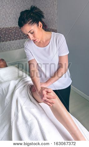 Portrait of female massage therapist doing lymphatic drainage massage on legs of young woman in a clinical center. Medicine, healthcare and beauty concept.