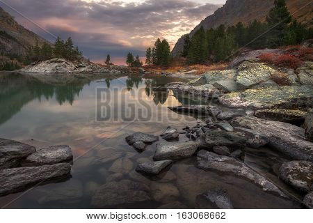Mountain Lake Sunset Coast With Pine Forest And Rocks, Altai Mountains Highland Nature Autumn Landscape Photo. Beautiful Russian Wilderness Scenery Image.