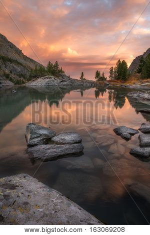 Rocks And Trees Reflecting In Pink Waters Of Sunset Mountain Lake, Altai Mountains Highland Nature Autumn Landscape Photo. Beautiful Russian Wilderness Scenery Image.
