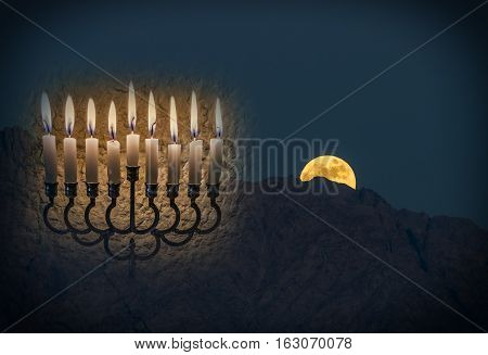Low key composite image with menorah with glitter lights of burning candles and rise of moon above mountains. Image symbolizes Jewish holiday of Hanukkah