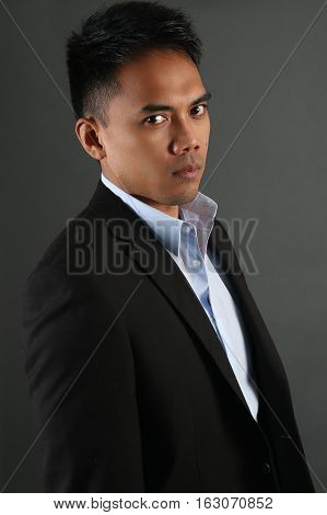 Malaysian businessman posing over a gray background