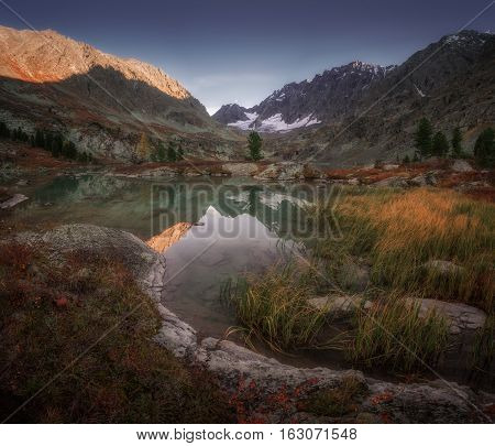 Small Mountain Lake View WIth Grassy Coast And Snowy Peaks, Altai Mountains Highland Nature Autumn Landscape Photo. Beautiful Russian Wilderness Scenery Image.