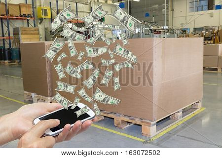 Female hands are holding some smart phone from which are flying banknotes. Cardboard boxes are standing in a designated place in the assembly hall in the background. All potential trademarks are removed.