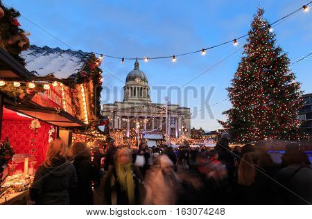 NOTTINGHAM ENGLAND - DECEMBER 22: Christmas tree and market and lots of people at Nottingham Christmas market. In Nottingham England. On 22nd December 2016.