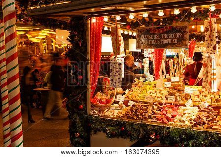NOTTINGHAM ENGLAND - DECEMBER 22: Man buying at sweet/candy stall at Nottingham Christmas market at night. In Nottingham England. On 22nd December 2016.