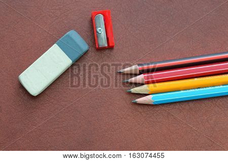 eraser writing pencils and a sharpener on a brown leather background