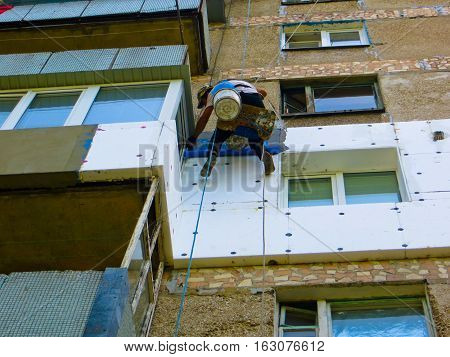 Rope access worker spreading mortar over the styrofoam insulation