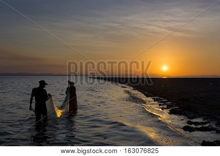 Ometepe Island Nicaragua - April 7 2014: Two fisherman fishing in the shores of the Ometepe Island in Lake Nicaragua Nicaragua at sunset
