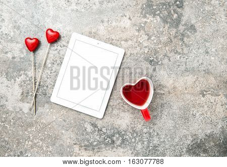 Tablet PC with red hearts decoartion and cup of tea. Valentines Day concept with space for your text and image