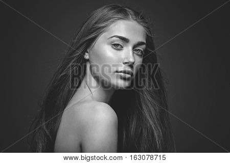 Beautiful young woman with straight healthy hair and natural make-up on dark background. Copy space. Monochrome.