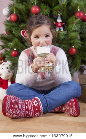 Little girl eating turron traditional spanish Christmas sweet. She is sitting close to Xmas Tree
