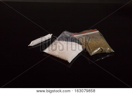narcotic packs and joint marijuana on black background