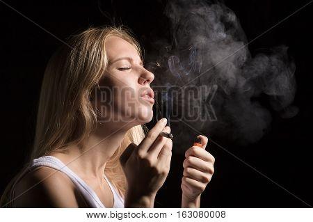 woman smoking joint of marijuana on black background