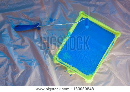 Blue rolling brush and green pallet with blue paint on pollythene