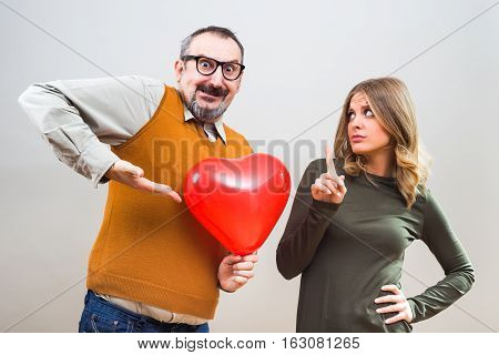 Nerdy man wants to give heart shape balloon to a beautiful woman to show her his love,but she is not interested.