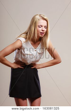 Bellyache indigestion or menstruation. woman suffering from stomach pain studio shot on gray