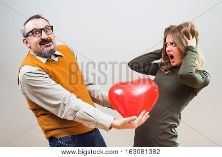 Nerdy man wants to give heart shape balloon to a beautiful woman to show her his love,but she is not interested,she is terrified.