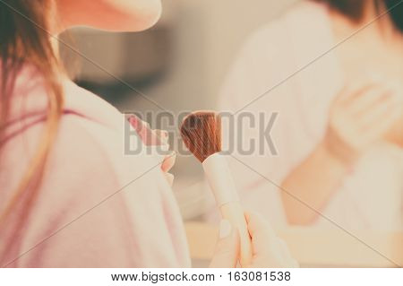 Woman Applying Bronzing Powder With Brush To Her Skin