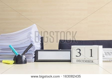 Closeup white wooden calendar with black 31 december word on blurred brown wood desk and wood wall textured background in office room view with copy space selective focus at the calendar poster