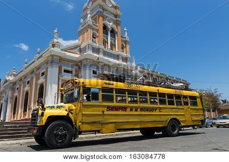 Granada Nicaragua - April 4 2014: Bus in front of a Church in a street of the colonial city of Granada in Nicaragua