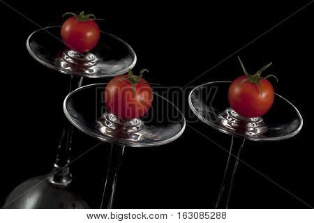 Red cherry tomatoes on the overturned glasses.