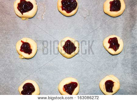 Unbaked cookies with jelly jam on baking paper in domestic kitchen. Flat lay top view.