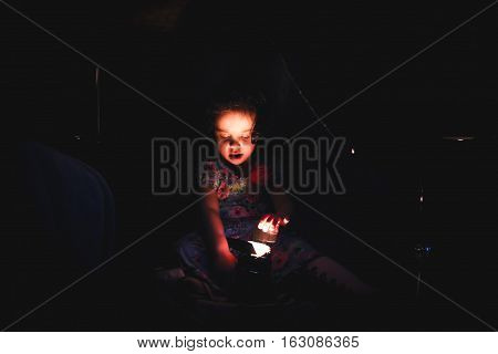 beautiful little girl in the dark with a lantern
