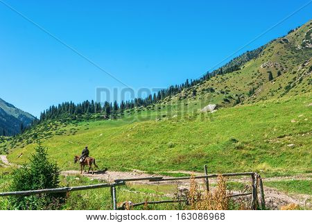 Beautiful Mountain Landscape With Horseman In The Foreground, Kyrgyzstan.