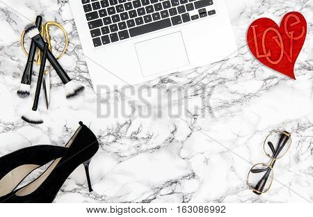 Feminine accessories notebook red heart decoration on office desk background. Fashion flat lay for blogger social media