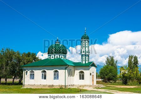 The white mosque with green dome in the village of Issyk-Kel Kyrgyzstan.
