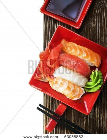 Japanese seafood sushi and chopsticks on a red plate