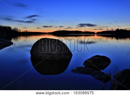 sunset on the rocky shore of the lake in the forest
