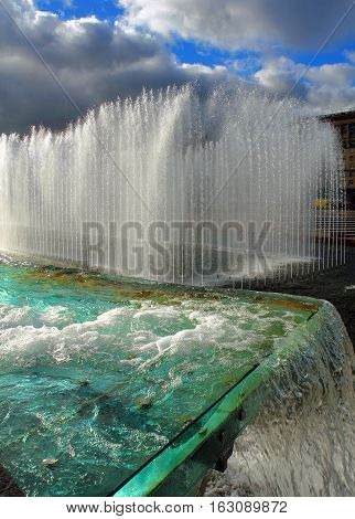 city fountain with blue water and the rainbow
