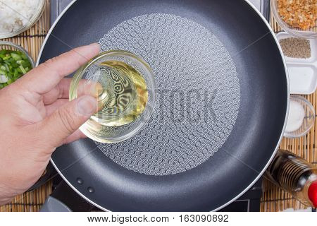 Chef putting oil to the pan / cooking fired rice concept