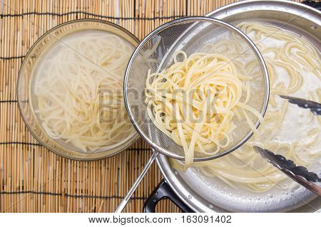 Spaghetti lifted on of cold water with tomgs / cooking spicy spaghetti concept