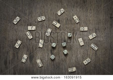 dice and dominoes on the wooden table background abstract