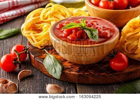 Products for cooking - tomato sauce pasta tomatoes garlic olive oil on the old wooden background.