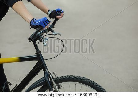Athlete holding hands handlebar. In the hands of put on blue gloves. Cycling. Healthy lifestyle.