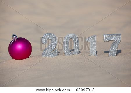 Four New Year's figures are in the sand on the beach or seaside cast a large shadow on the ground. Near the sand is pink ball. New Year Celebration and Christmas in the ocean the sea. Traveling.