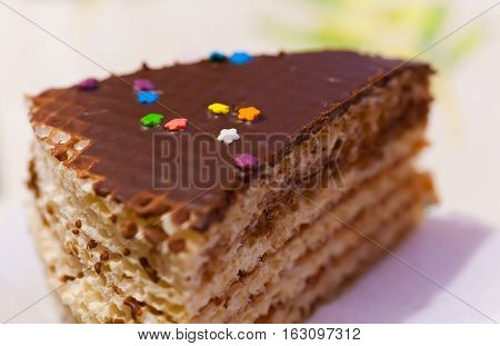 A piece of birthday cake. Puff waffle cake with jam and condensed milk. Top cake covered with sweet pastry with chocolate icing and colorful confetti.