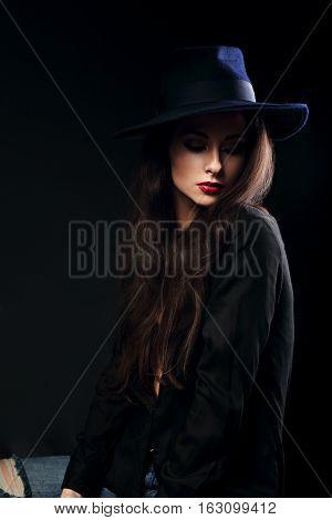 Expressive Female Makeup Model Posing In Black Shirt And Elegant Hat With Red Lipstick On Dark Backg