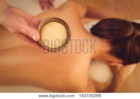 Top view close up of masseuse hand holding fenugreek in bowl. Young woman is lying on background