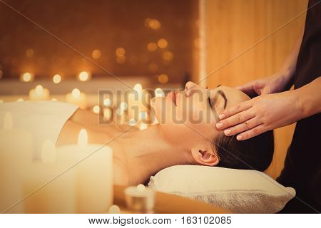 Skillful beautician is massaging female temples at wellness center. Serene girl is lying with pleasure. Burning candles create relaxing atmosphere