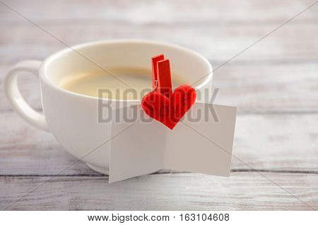 Cup of fresh morning coffee with Valentine's day card, selective focus, horizontal, copy space.